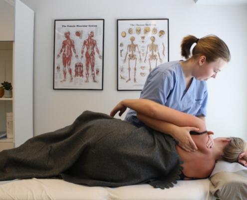 Bilde fra klinikk hvor osteopat Elisabeth behandler en kvinnelig pasienten liggende på siden. Hun holder to hender rundt skulderen til pasienten og utfører mobilseringsteknikker. To muskel- og skjelett plakater i bakgrunn.