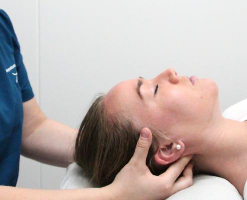 Osteopat Elisabeth behandler øvre del av nakken for smerter og hodepine.