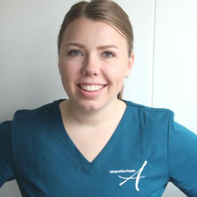 Osteopat Elisabeth smilende i blå uniform med logo til akupunkturhuset.